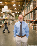 Businessman in warehouse. The man, who is of possible Hispanic descent, is smiling at the camera. He is handsome and wearing a blue dress shirt and a neck tie.  Shelves lined with pallets of materials.